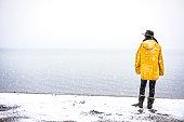 Female traveler with yellow rain coat enjoying snowy day
