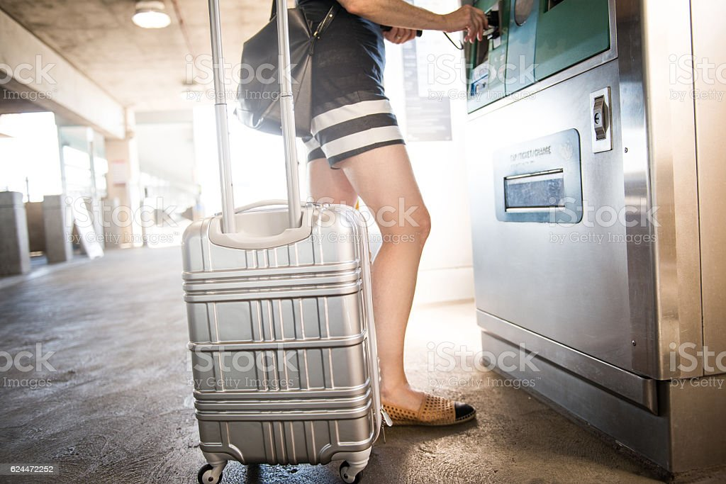 Female Traveling Alone with Suitcase Buys Ticket stock photo