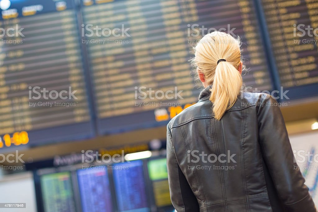 Female traveller checking flight departures board. stock photo