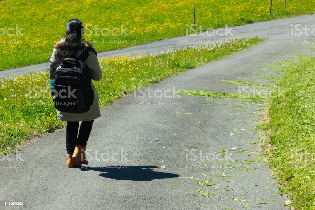 Female traveller with backpack walking along trail of green road stock photo