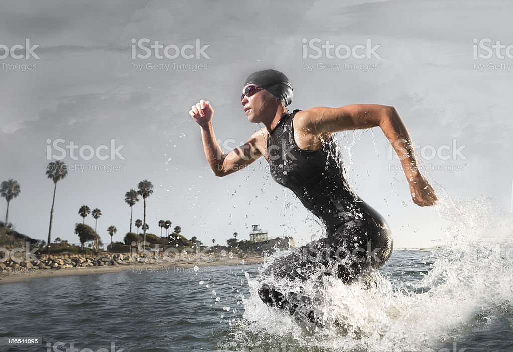 Female Triathlon Athlete rushing out of the water stock photo