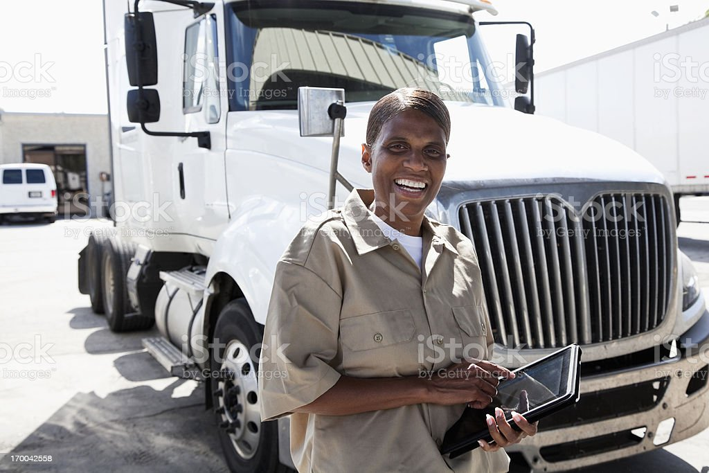 Female truck driver by big rig with digital tablet stock photo