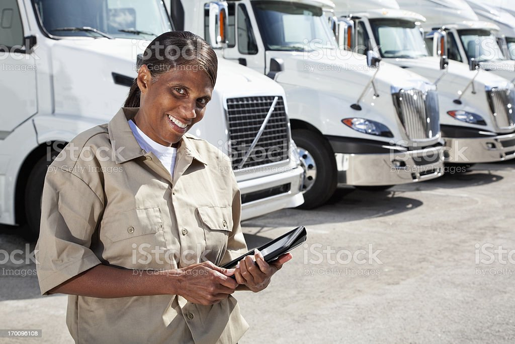 Female truck driver by big rigs with digital tablet stock photo