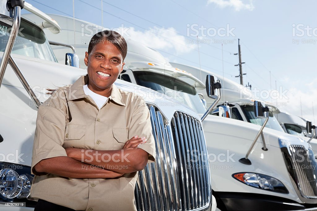 Female truck driver standing by semi-trucks stock photo