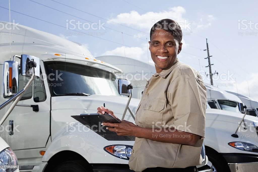 Female truck driver standing by semi-trucks with clipboard stock photo
