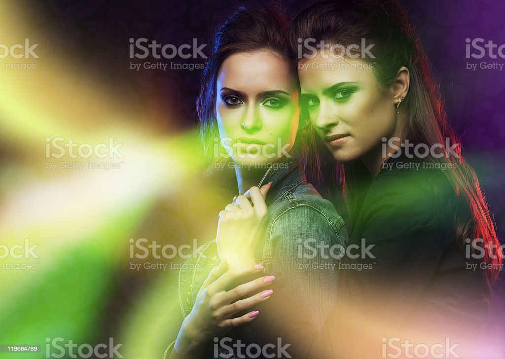 Female twins in colored light stripes. royalty-free stock photo