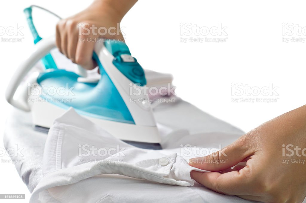 A female using an iron to iron a shirt stock photo