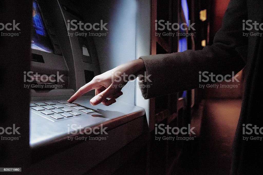 Female using  ATM at night on the street stock photo
