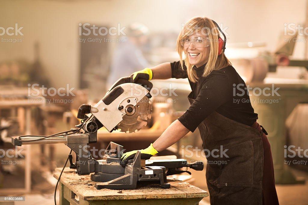 Female using circular saw stock photo