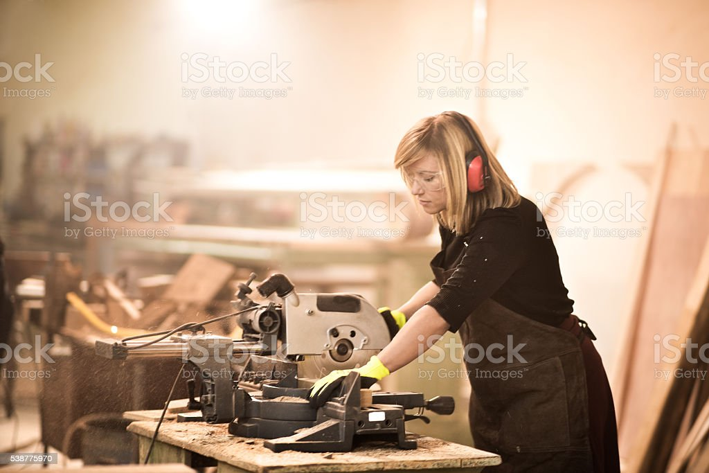 Female using circular saw stock photo