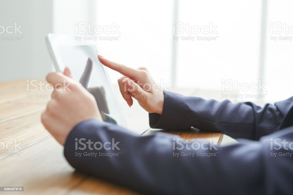Female using digital tablet, close up, side view, stock photo