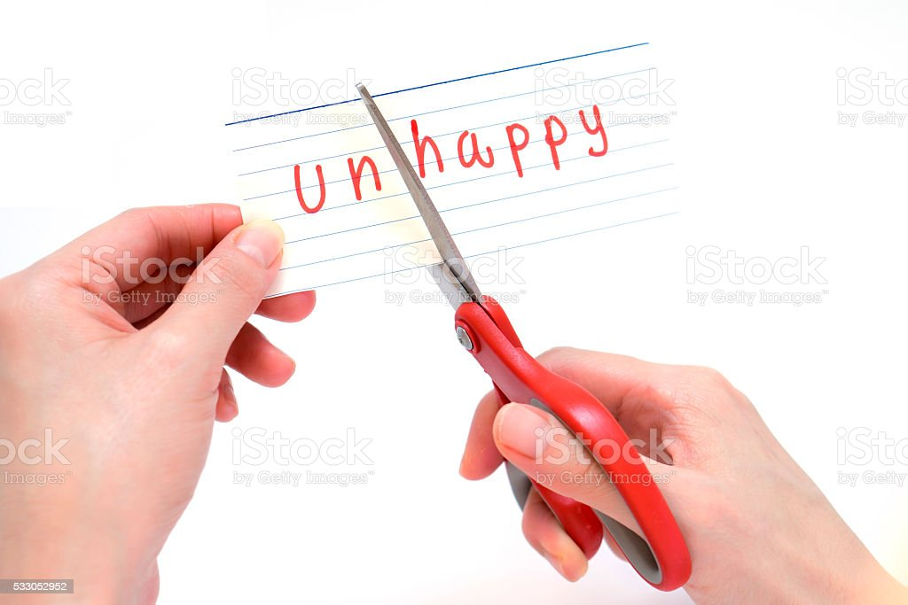 Female using scissors to remove the word unhappy stock photo