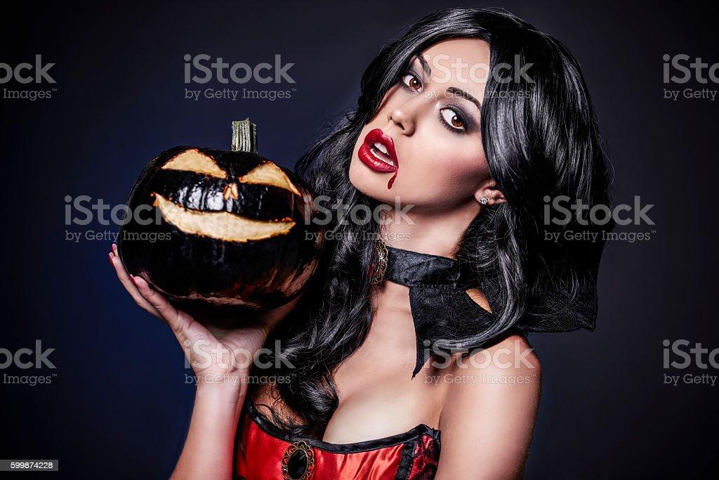 Female vampire and black pumpkin stock photo