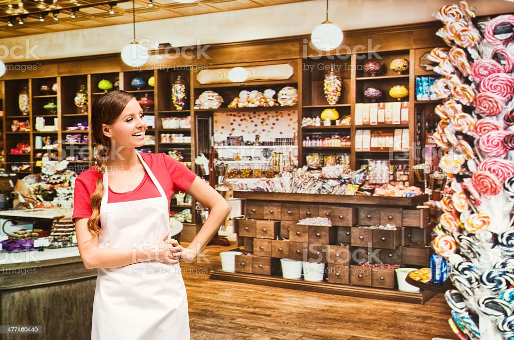 Female vendor standing at candy shop stock photo