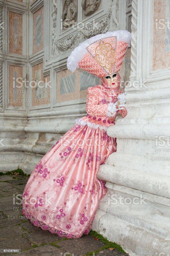 Female Venetian Mask in light pink elegant carnival costume at Venice Carnival. stock photo