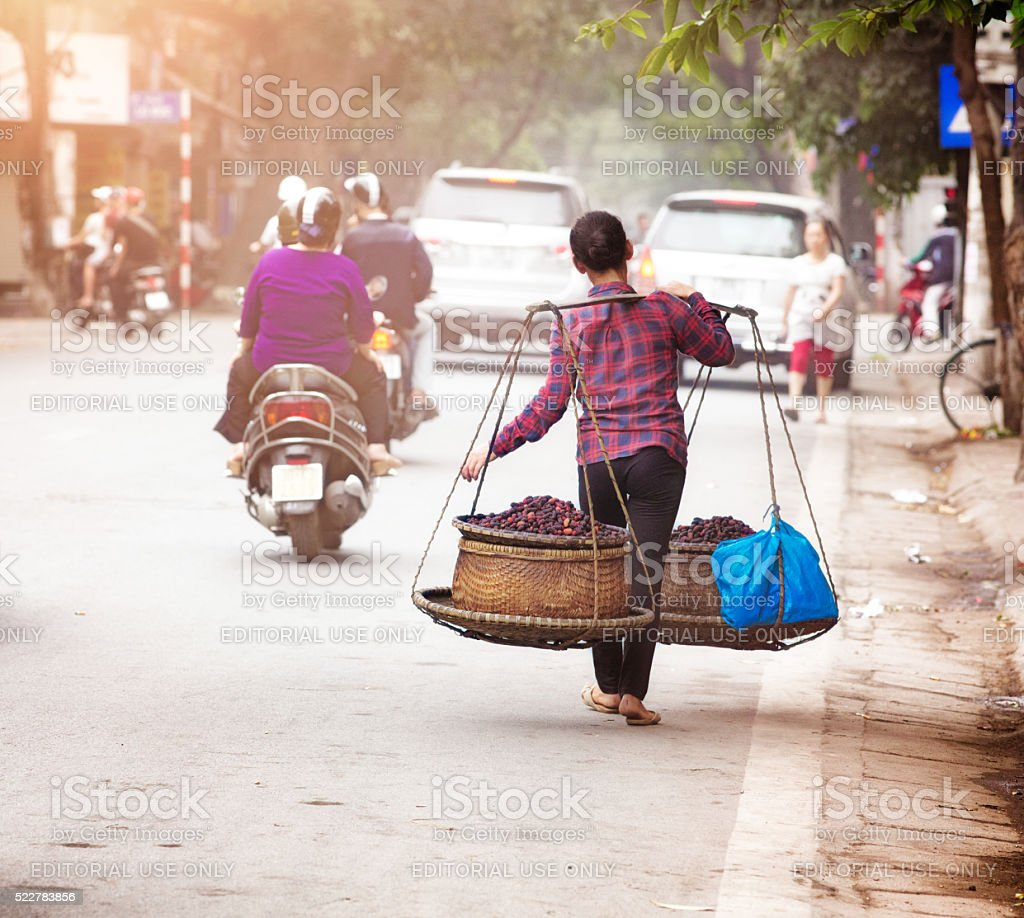 Female Vietnamese street merchant carrying her food by foot stock photo