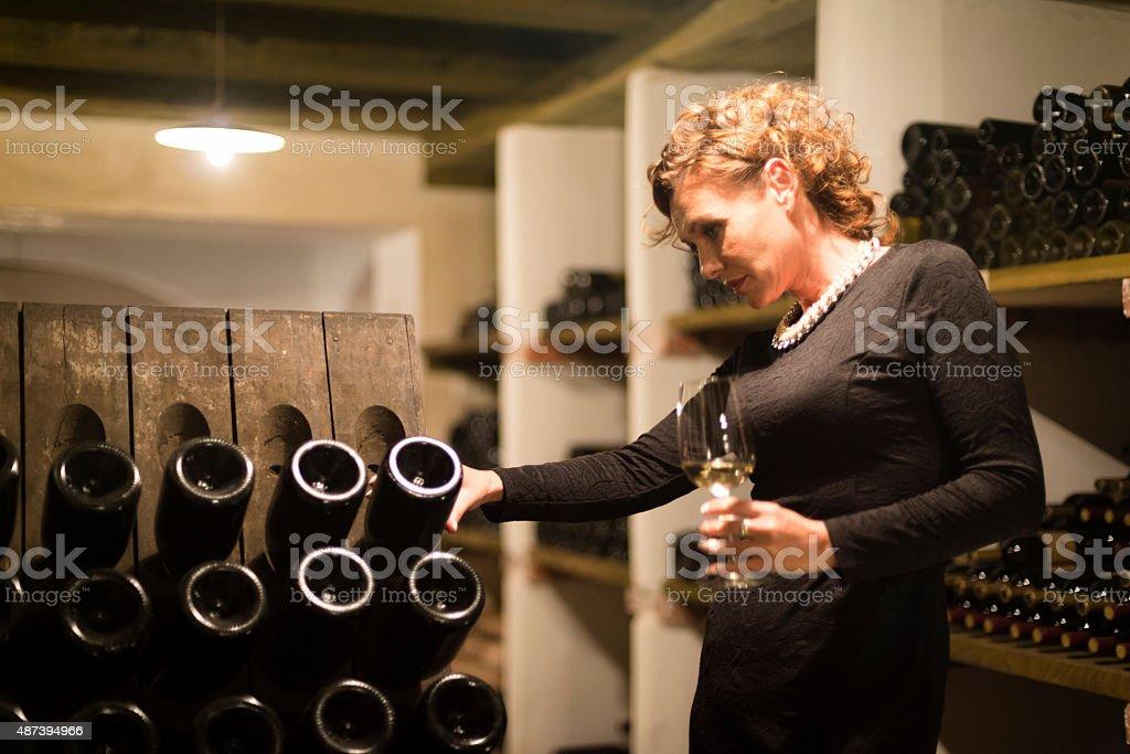 Female Vintner Checking Champagne Bottles, Cellar in Europe stock photo