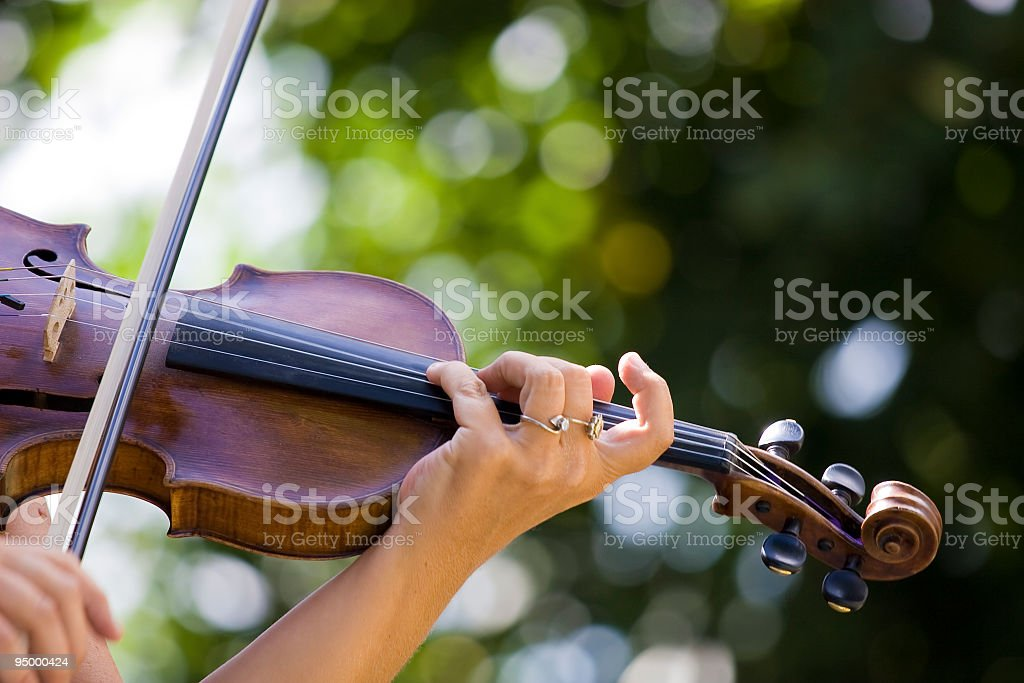 Female violinist playing outdoors on a sunny day stock photo
