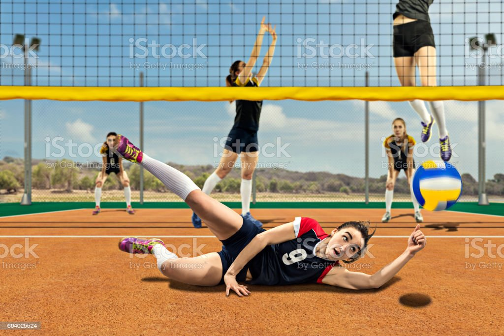 Female volleyball player reaching the hard ball on the ground