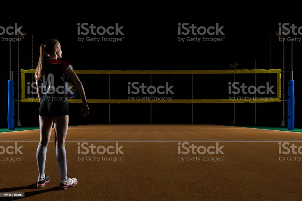 Female volleyball player holding the ball on volleyball field at night