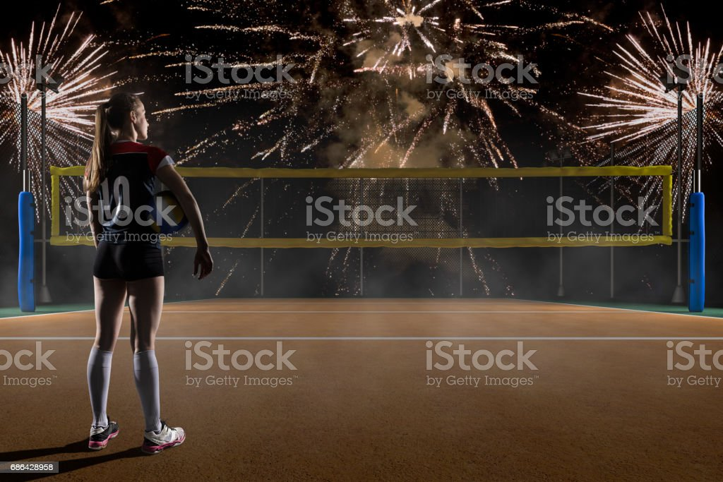 Female volleyball player holding the ball on volleyball night field...