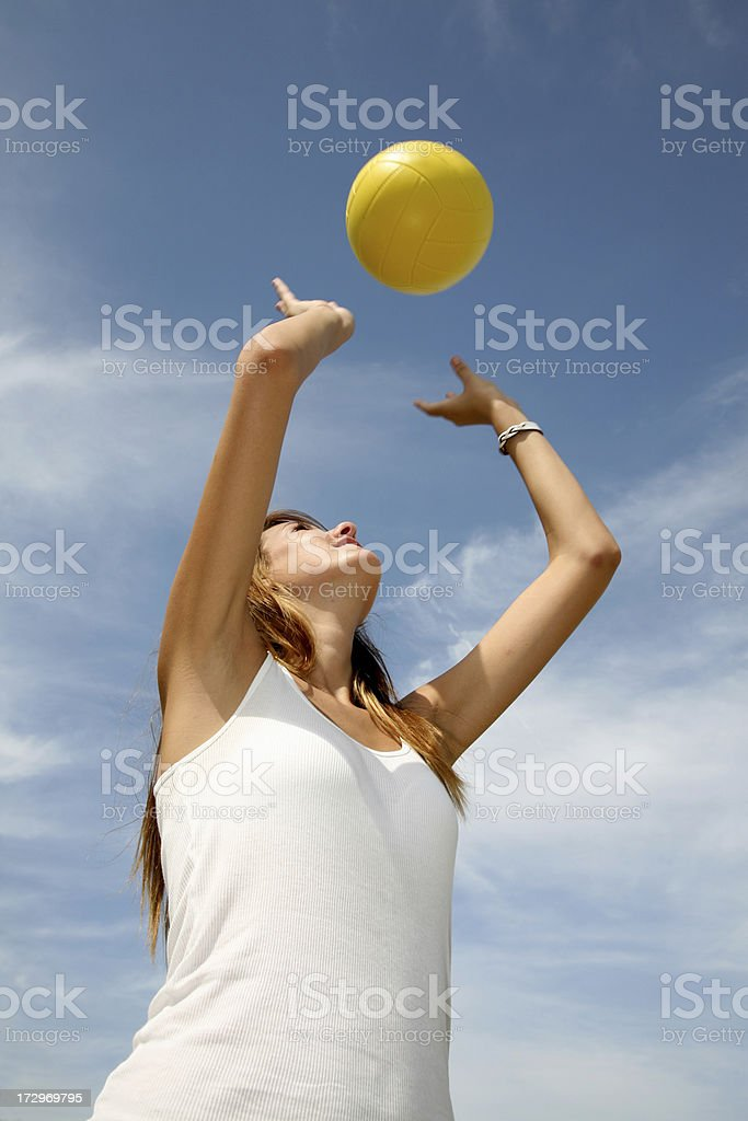 Female Volleyball Player Throws Yellow Ball Into The Blue Sky royalty-free stock photo