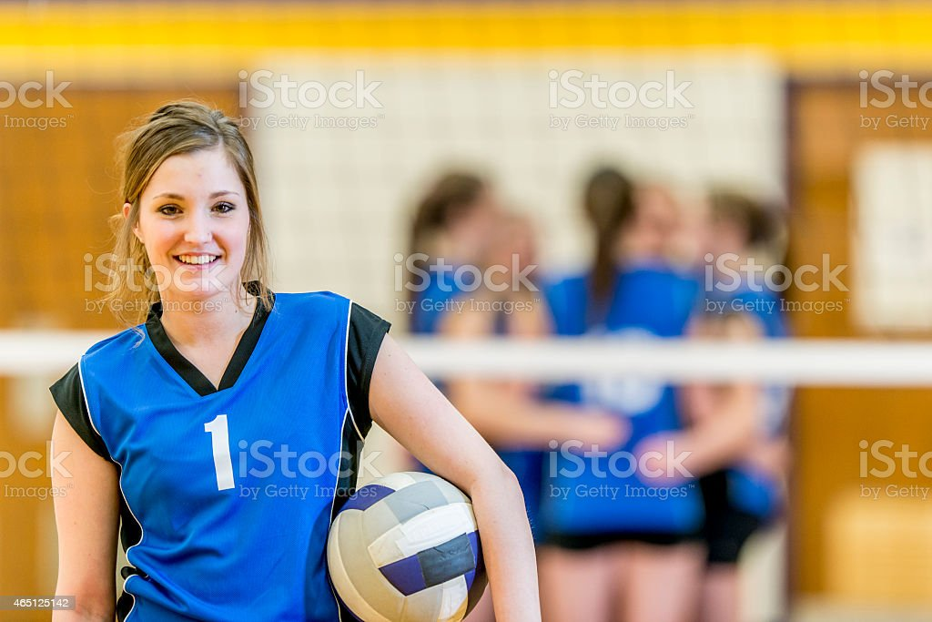 Female volleyball player with team in background stock photo