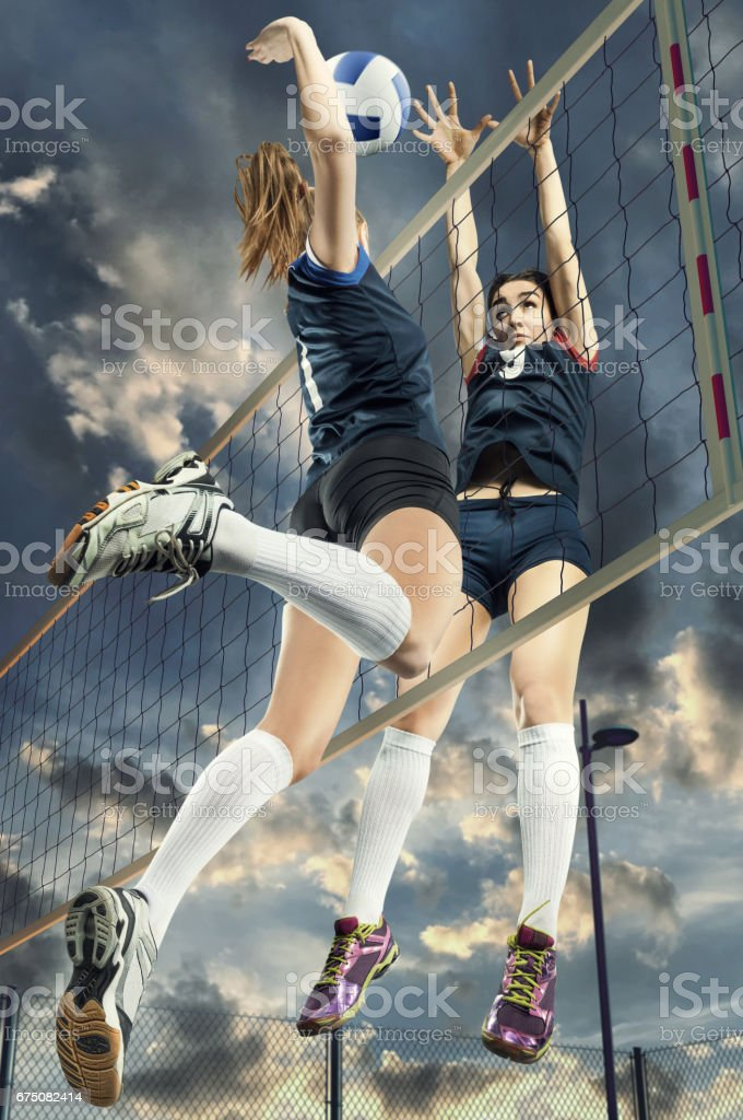 Female volleyball players jumping close-up stock photo