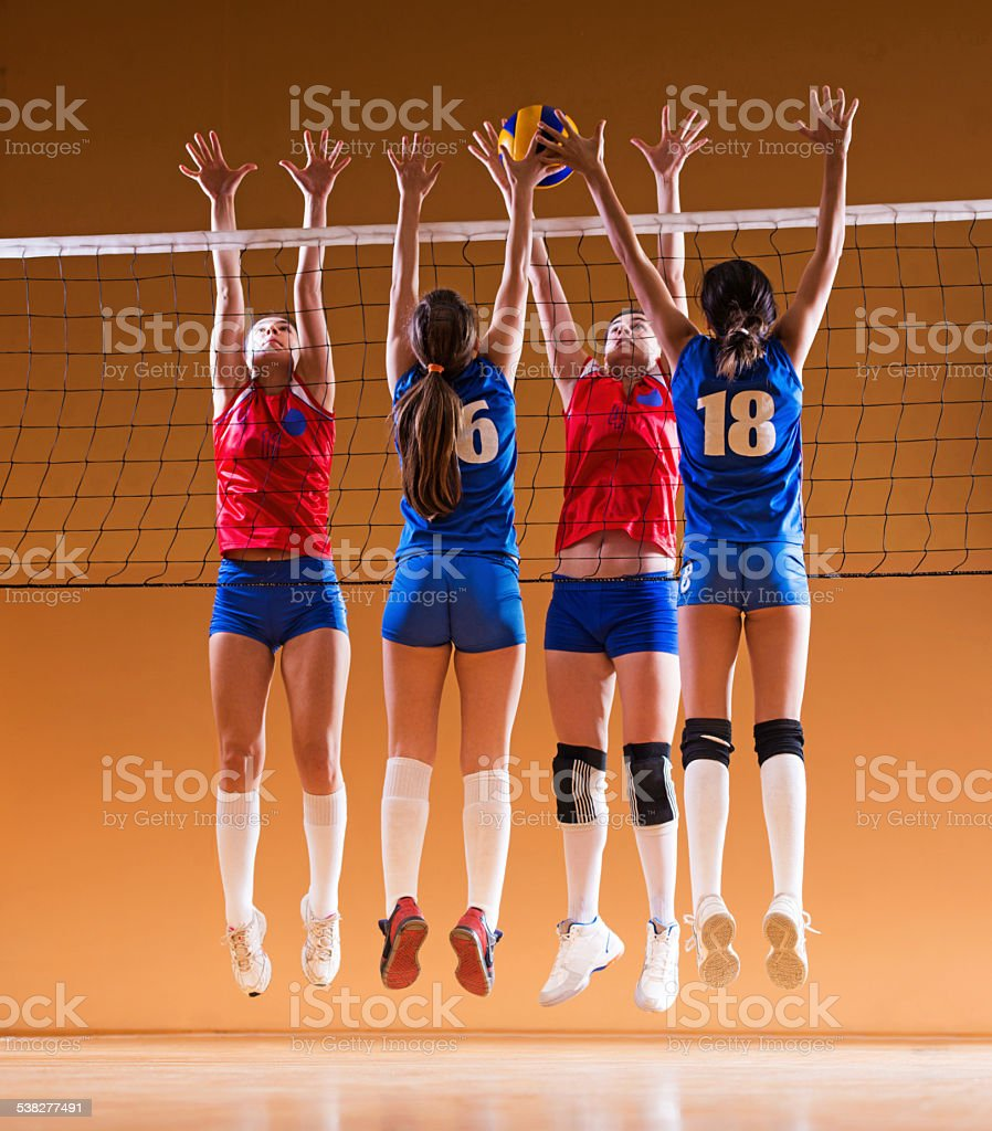 Female volleyball team in action. stock photo