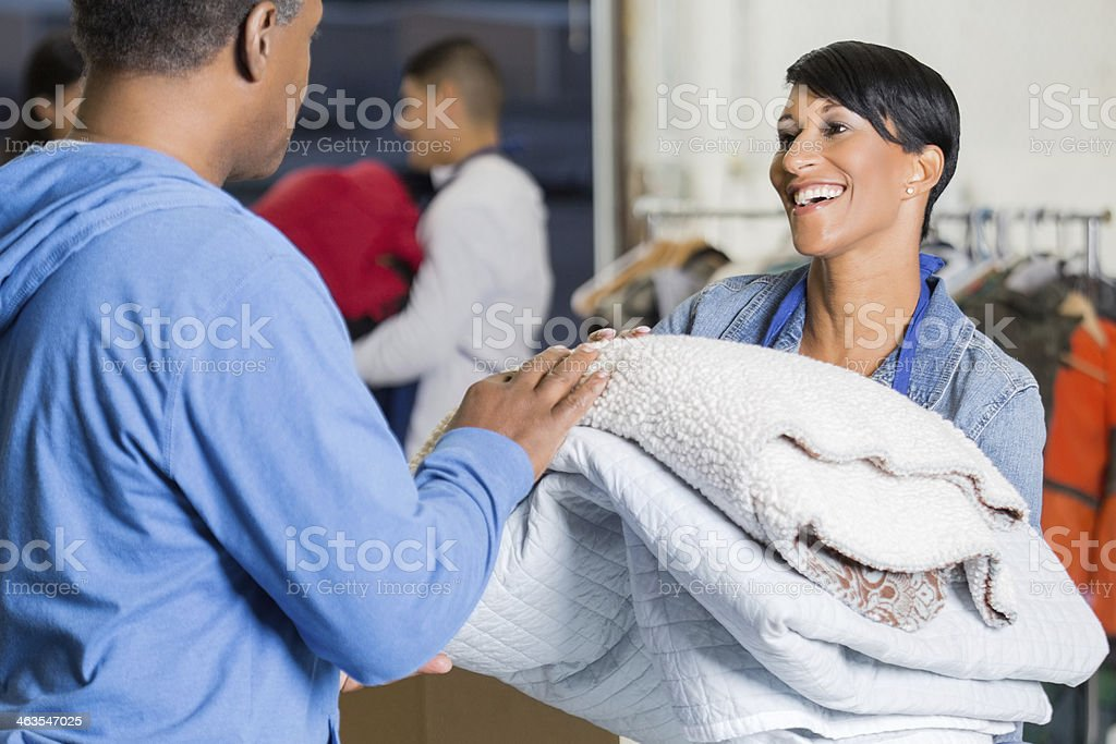 Female volunteer giving donated blankets to disaster victim stock photo
