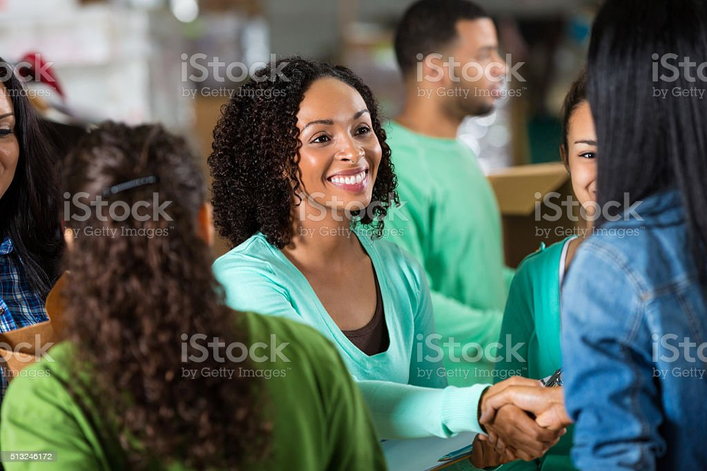 Female volunteer greets woman in food bank stock photo