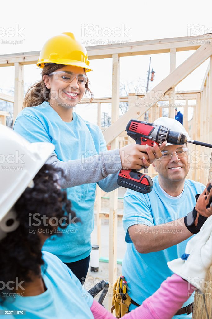 Female volunteer uses power drill at construction site stock photo
