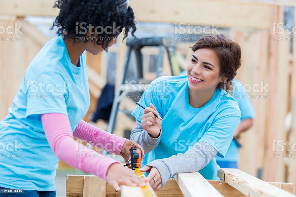 Female volunteers talk while working on charity home stock photo