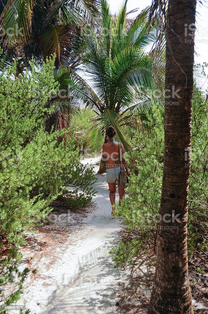 Female walking green island beach path, San Andres, Caribbean, Colombia. stock photo