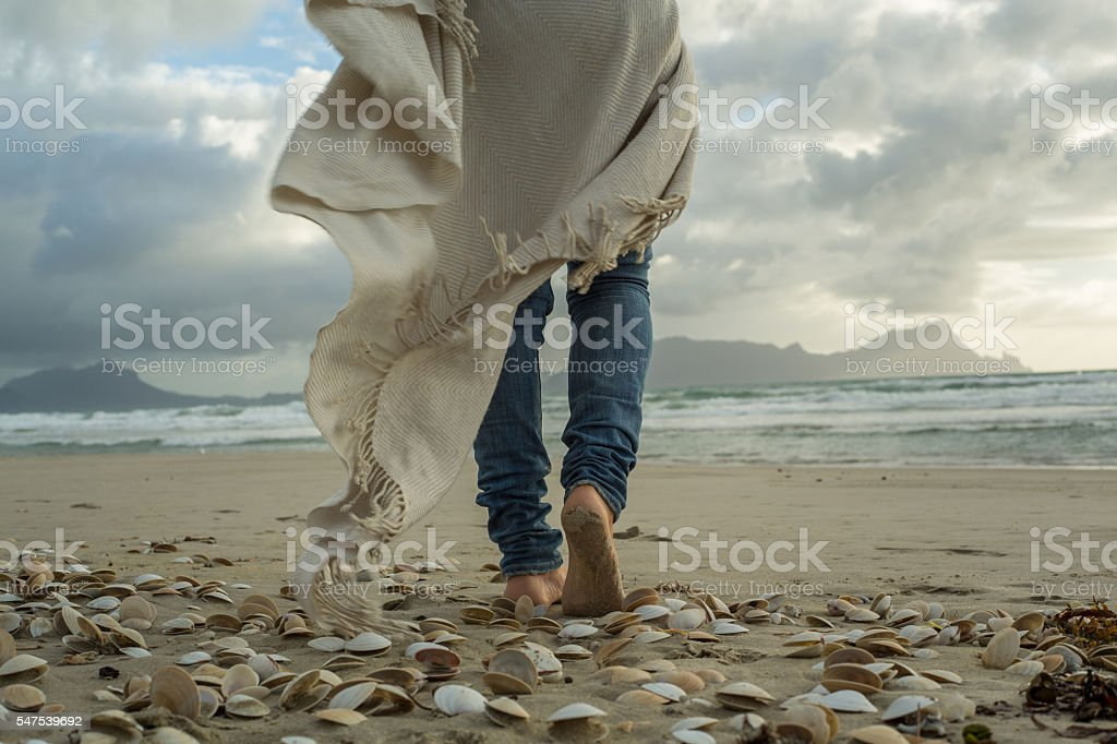 Female walking on beach at sunset stock photo