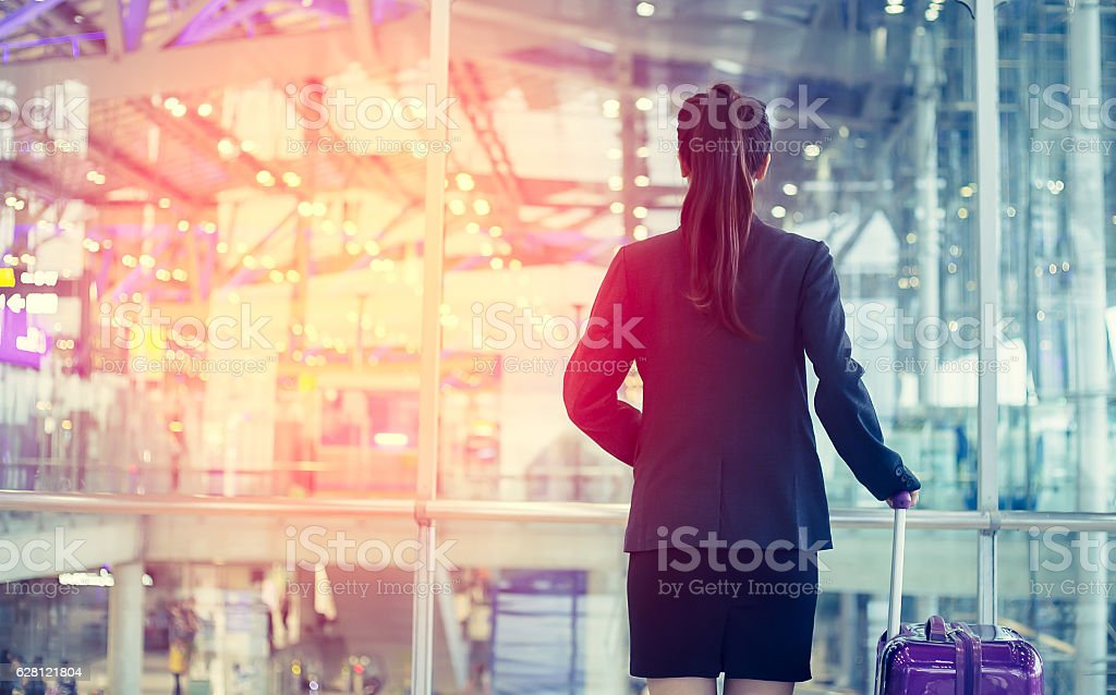 Female walking through the airport using her smartphone device. stock photo