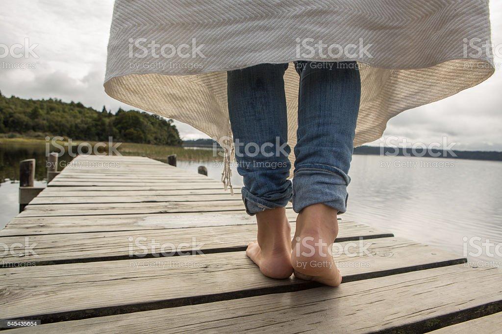 Female walks on jetty above lake stock photo