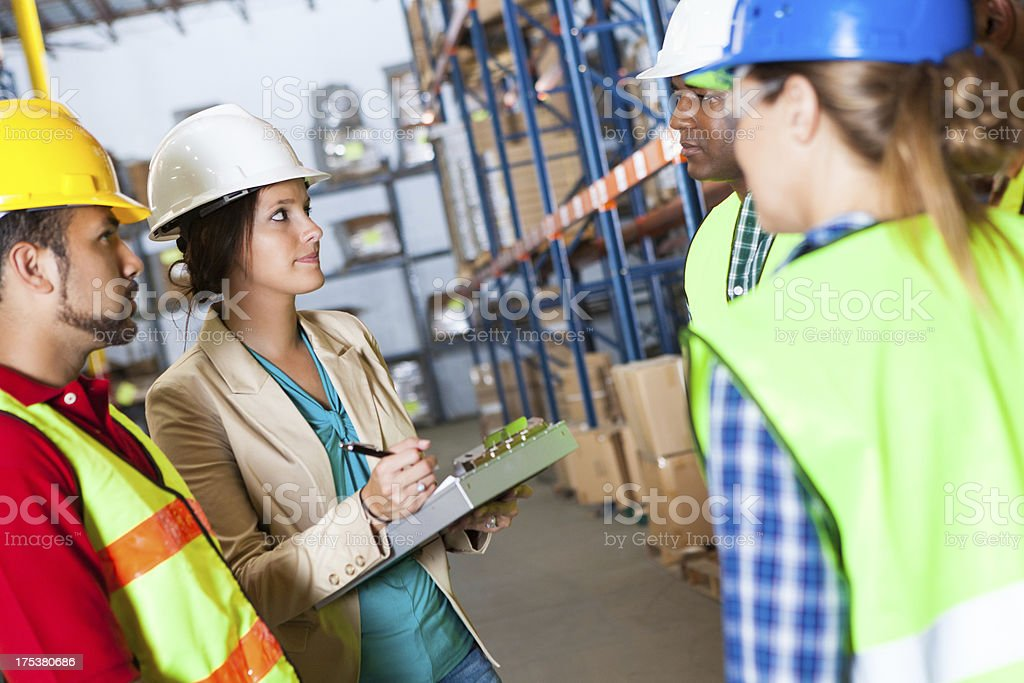 Female warehouse manager discussing shipping order with employees royalty-free stock photo