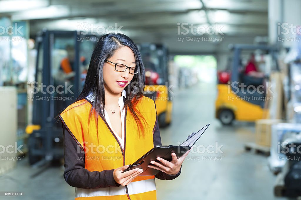 Female warehouse worker looking at tablet PC stock photo
