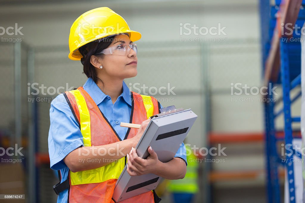 Female warehouse worker taking inventory with clipboard stock photo
