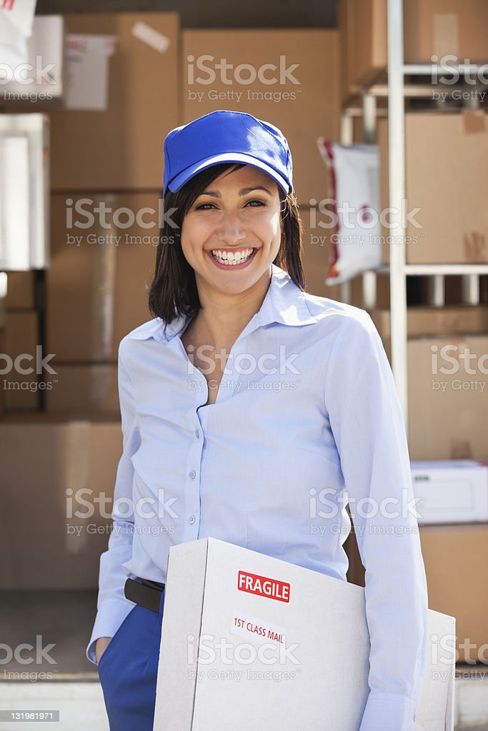 Female warehouse worker with box in hand stock photo