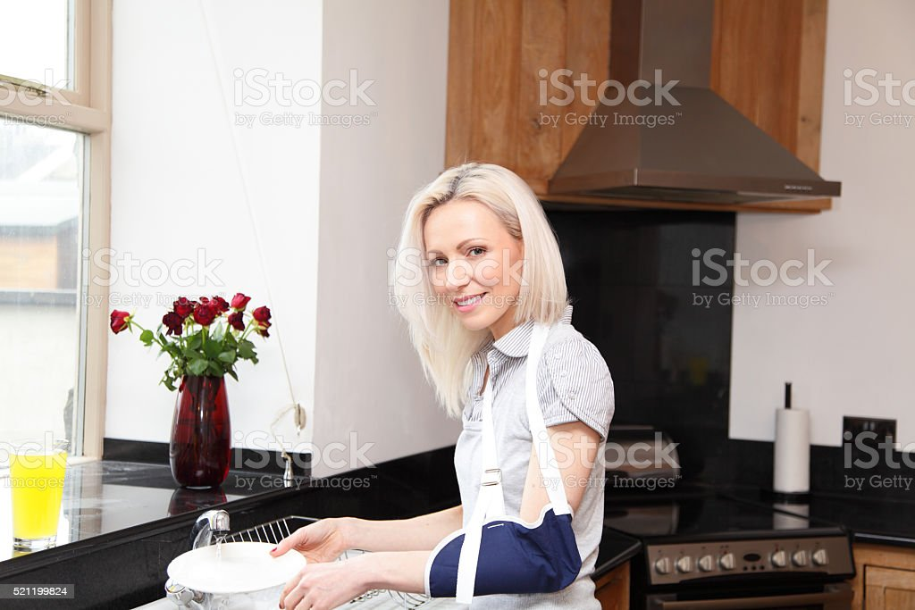 female washing dishes with broken collorbone stock photo