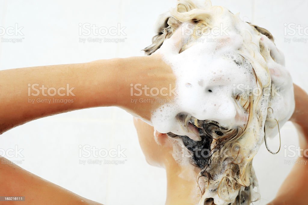 Female washing hair by shampoo. stock photo