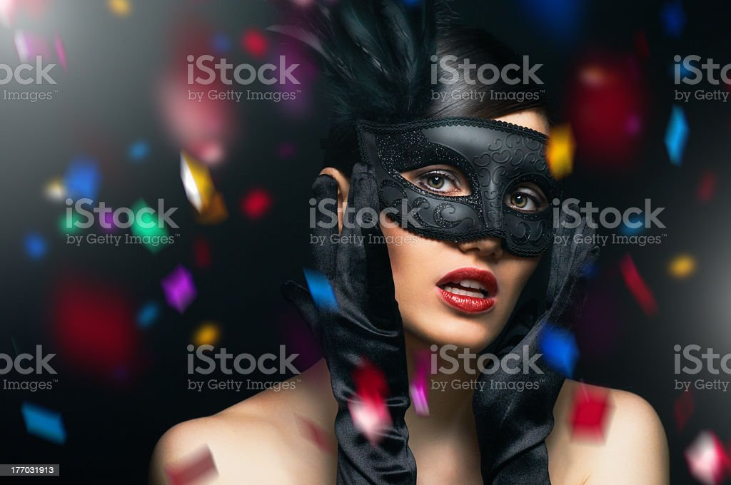 Female wearing a black masquerade mask with confetti falling stock photo