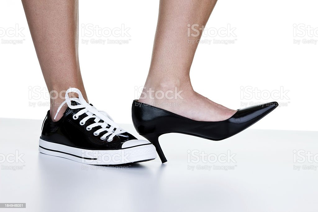 Female wearing a dress shoe and sneaker stock photo