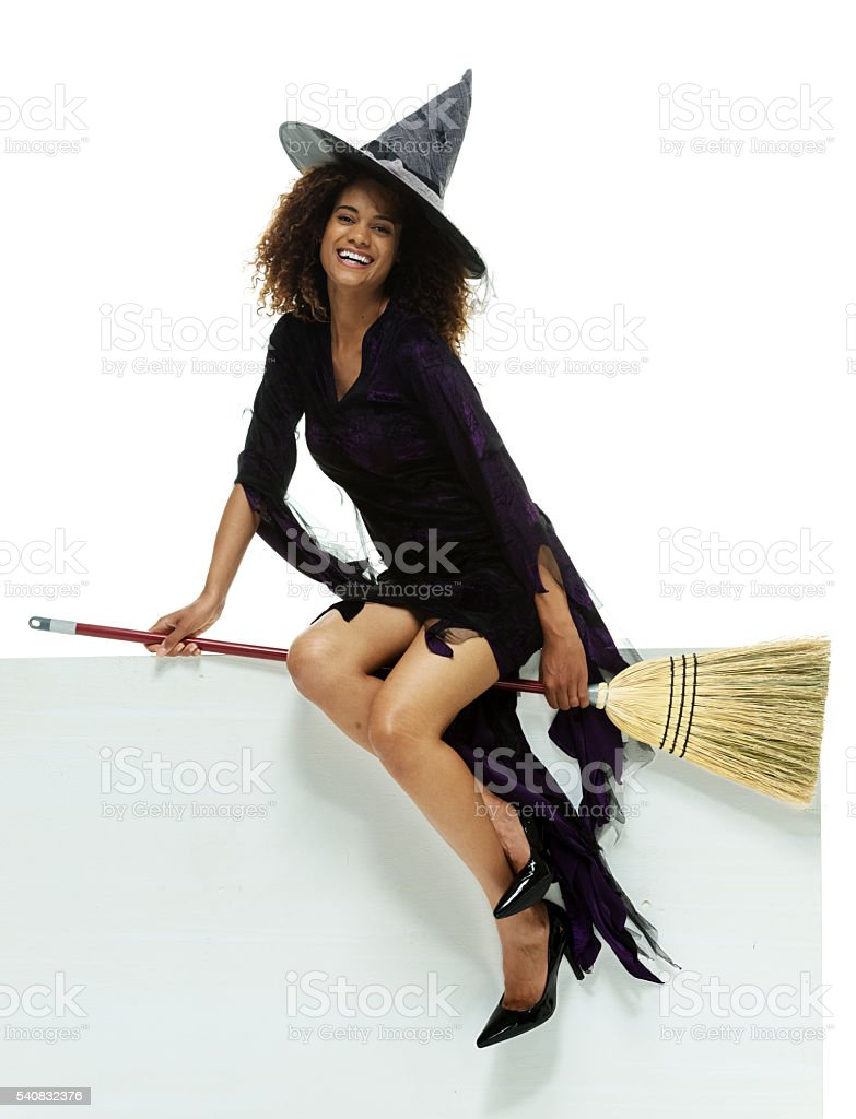 Female witch pretending to sit on a broom stock photo