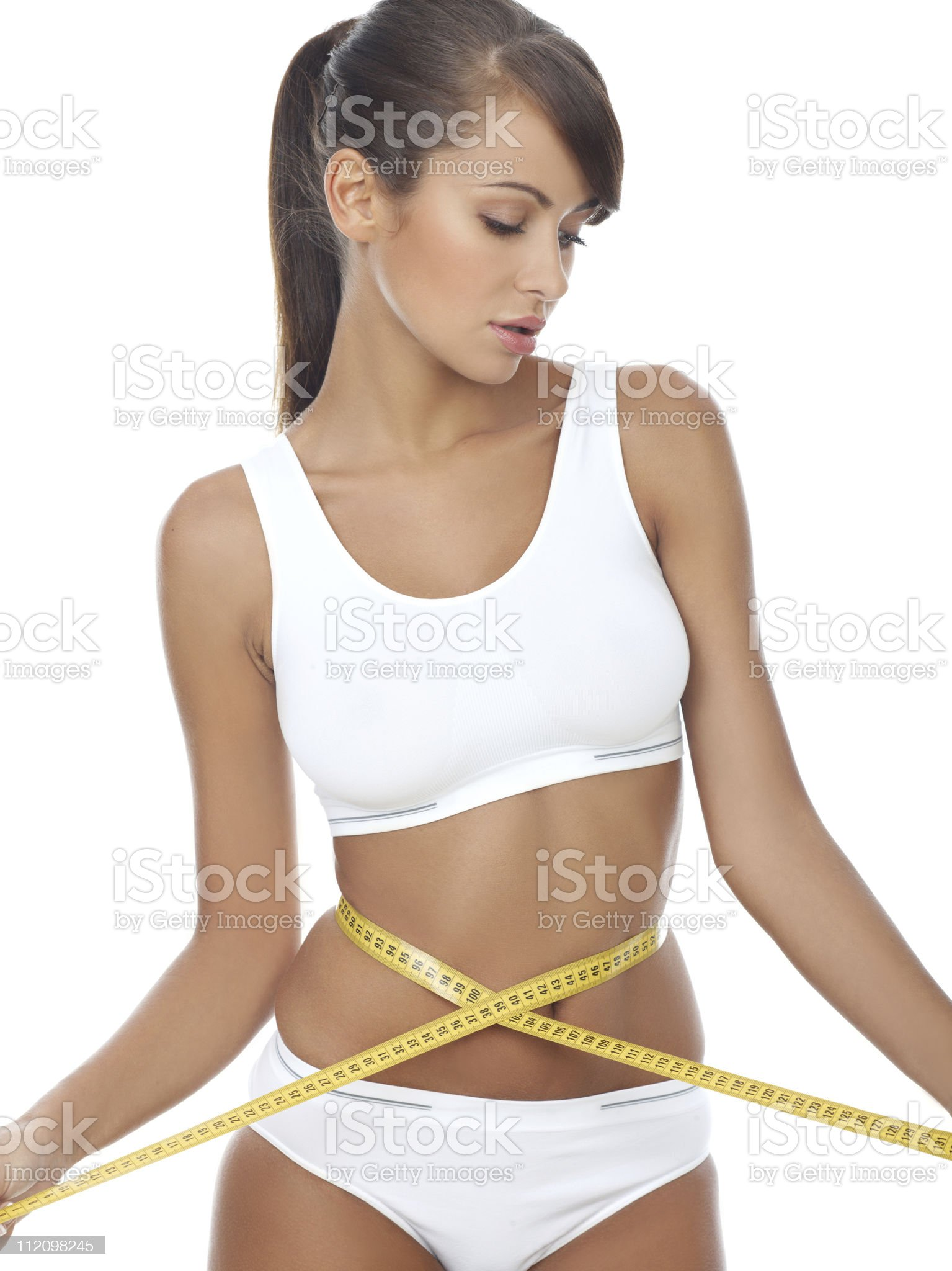Female with a measuring tape around her tiny waist royalty-free stock photo