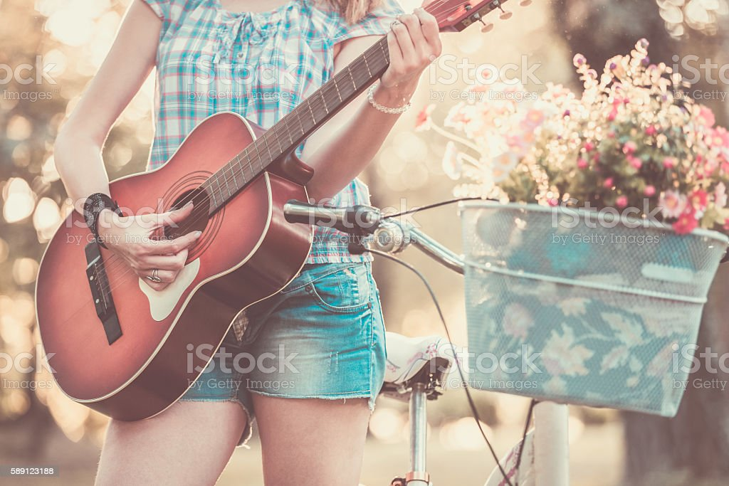 Female with acoustic guitar in nature stock photo