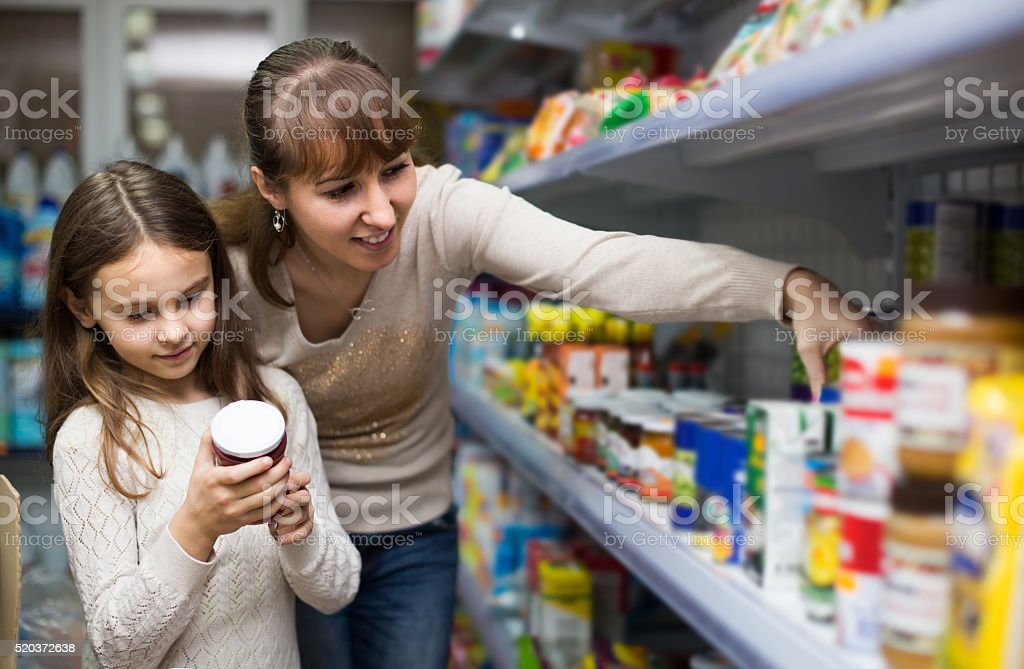female with daughter choosing canned goods in food store stock photo