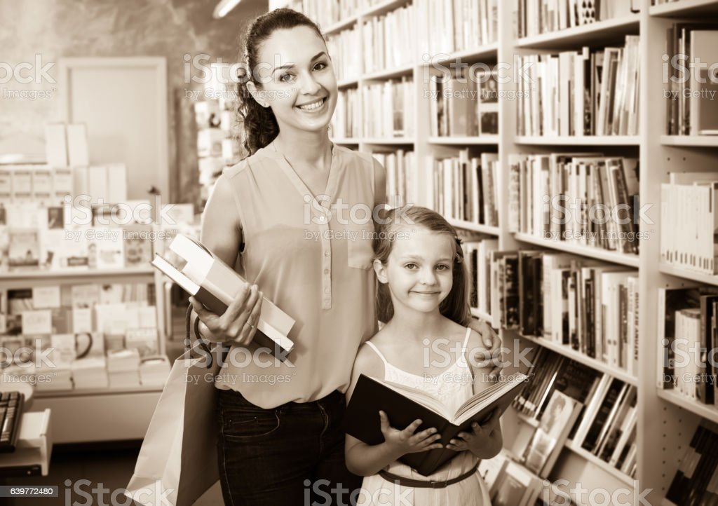 Female with smiling girl in school age picking books stock photo